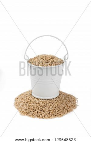White bucket full of sesame stands on a heap sesame on a white background