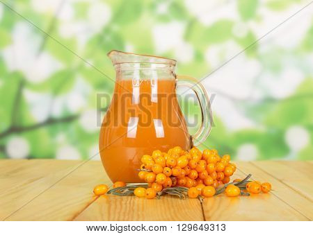 Sea buckthorn juice on the table and the background of green leaves
