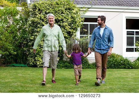 Father and son walking while holding hands with boy at yard