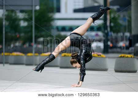 Beautiful woman performing acrobatics in the city