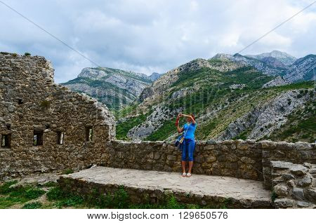 Young woman on fortress walls of the citadel photographs the view in the vicinity of Bar Montenegro