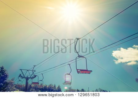 Sunset and  Ski lift going over the mountain ( Filtered image processed vintage effect. )