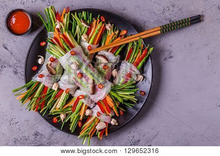 Spring rolls with vegetables and shiitake mushrooms on a plate, top view.