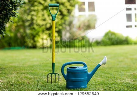 Close-up of rake and watering can on grass in yard