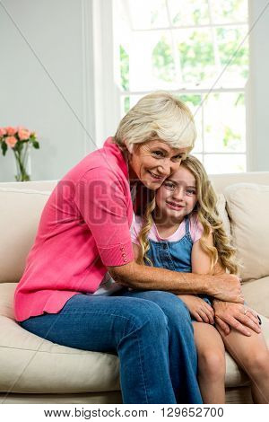 Smiling granny and girl hugging while sitting on sofa at home