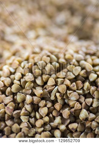 brown buckwheat close up on a tablespoon in a glass