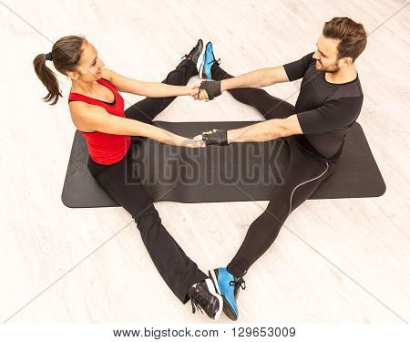Bird eye view of a young happy couple doing together stretching exercises on the floor in a gym.