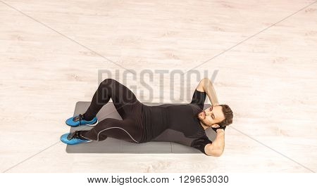 Bird eye view of a young man doing sit-ups on the floor in a gym.
