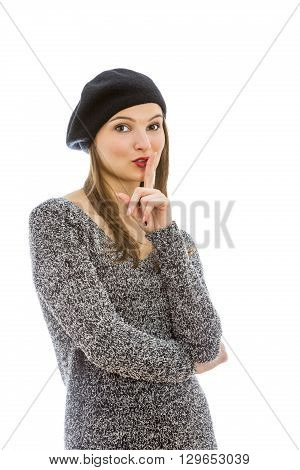 Portrait of a young woman with a silence gesture isolated against a white background.
