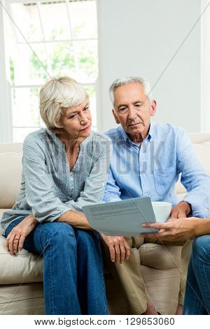 Cropped image of consultant showing report to senior couple at home