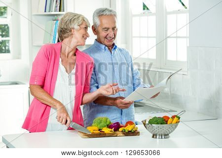 Smiling senior couple with recipe book while preparing vegetables in kitchen