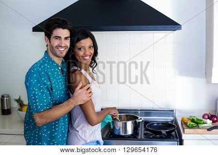 Man embracing woman while cooking in kitchen at home