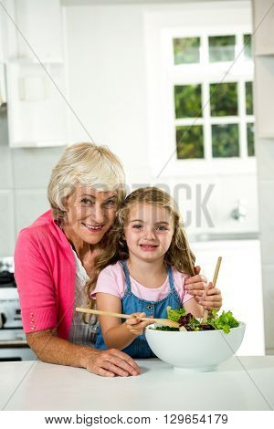 Portrait of happy granny and girl preparing vegetables in kitchen
