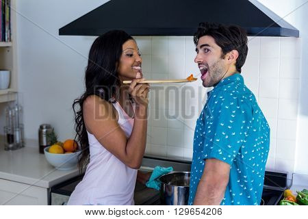 Woman feeding man while cooking in kitchen at home