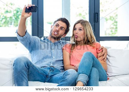 Young couple making faces while taking selfie at home