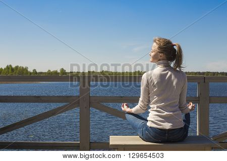 Yoga and meditation concept. Woman sitting in lotus position in front of lake