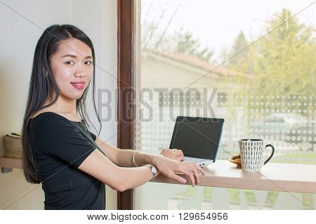 Young asian woman by lap top with a coffee