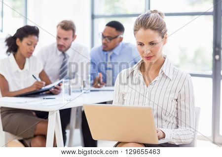 Businesswoman using laptop in office while colleagues discussing in background