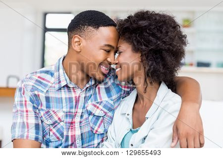 Young couple embracing each other in kitchen at home