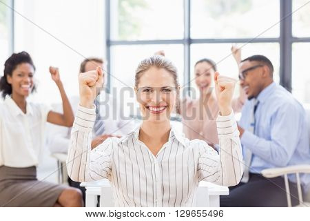 Portrait of businesswoman celebrating success in office with her colleagues