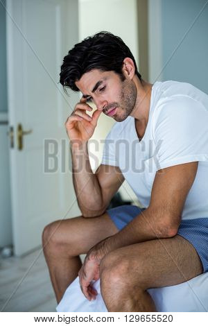 Tensed man sitting on bed in bedroom at home