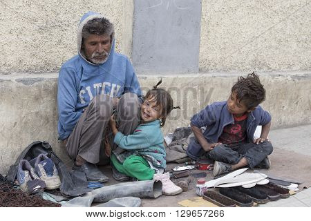 LEH INDIA - SEPTEMBER 08 2014: An unidentified beggar family begs for money from a passerby in Leh. Poverty is a major issue in India