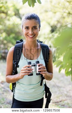 Woman smiling and holding binoculars on the wood