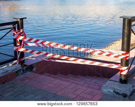 blocked access to the river. cordon tape. crossing barrier tape insulates a dangerous place on the river bank