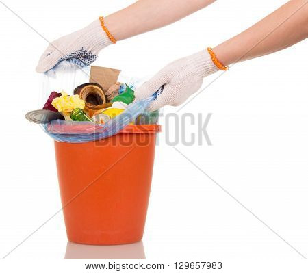 Hands lift the trash bag out of a bucket on a white background, close-up