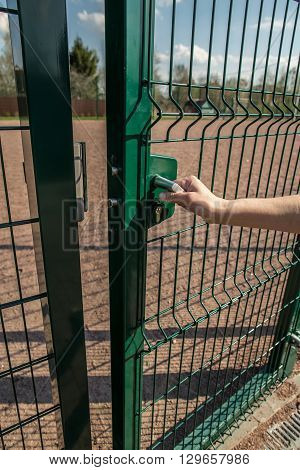 person wants get in on playground through the little gate of the welded wire mesh is green wonderful spring sunny day
