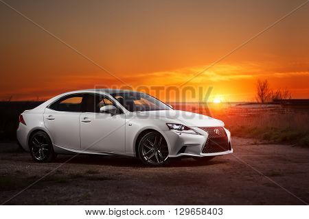 Saratov, Russia - May 08, 2014: White modern car Lexus IS250 stay on road at beautiful sunset