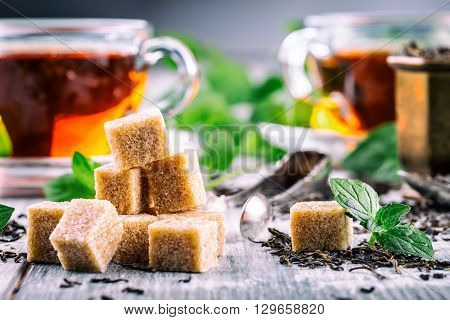 Sugar. Cane sugar. Cane sugar cubes heap close up macro shot. Tea in a glass cup mint leaves dried tea sliced lime cane brown sugar.