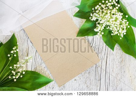 bouquet of lilies of the valley with a veil on an old white wooden background with a blank sheet of paper