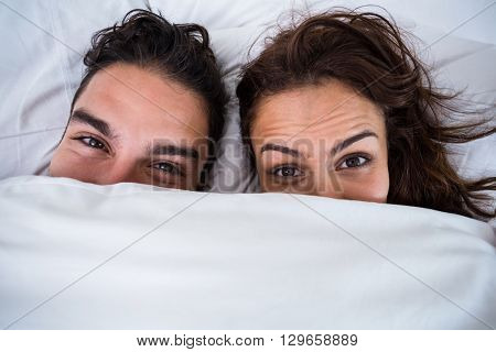 Close-up portrait of couple relaxing on bed at home