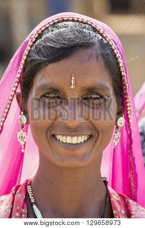 PUSHKAR INDIA - OCTOBER 28 2014: Unidentified woman looks on as she attends the annual Pushkar Camel Mela. This fair is the largest camel trading fair in the world.