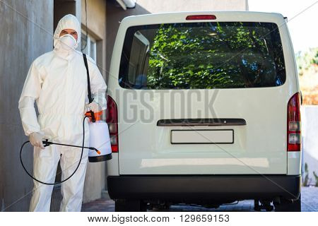 Pest control man in protective workwear standing behind a van
