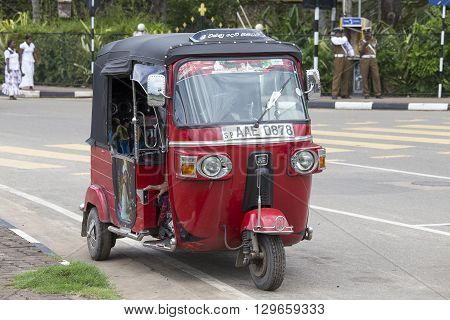 MATARA SRI LANKA - NOVEMBER 5 2014: Auto rickshaw or tuk-tuk on the street of Matara. Most tuk-tuks in Sri Lanka are a slightly modified Indian Bajaj model imported from India.