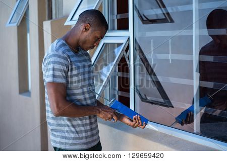 Man using pest control injection on the windows