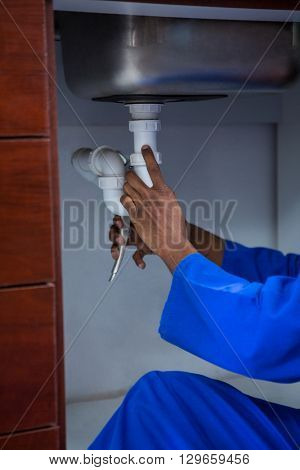 Plumber repairing a sink in kitchen