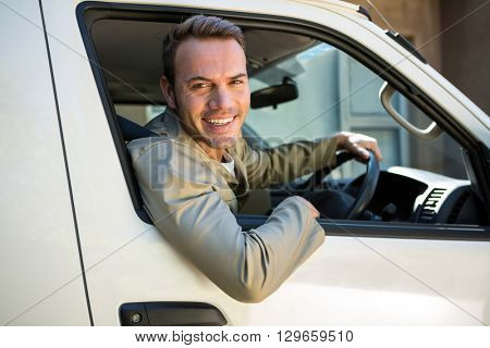 Delivery man smiling at camera while driving his van