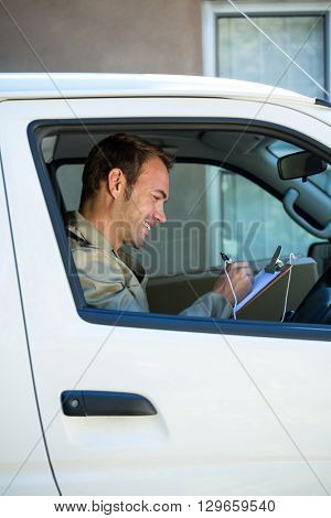 Delivery man writing on clipboard while sitting in his van