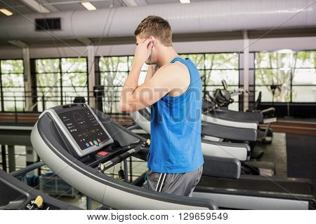 Man on treadmill listening to music at gym