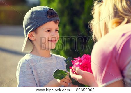 Happy little boy give flower to mom vintage mother's day motherhood