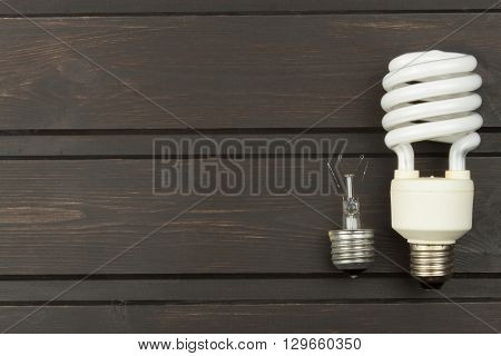 Broken incandescent bulbs and new energy-saving light bulb on wooden background. Sales of light bulbs. Advertising on lighting technology.
