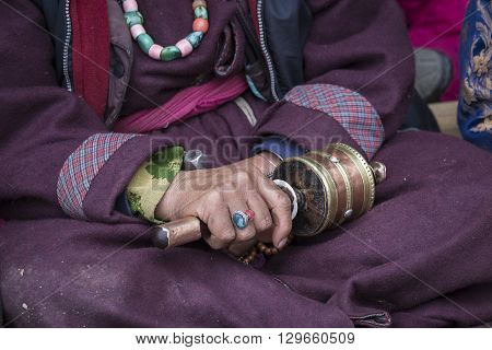 Old Tibetan woman holding buddhist prayer wheel in Lamayuru Gompa Ladakh India. Hand and prayer wheel close up