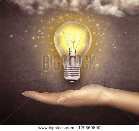 light bulb glowing on the hand isolated on dark background