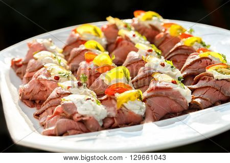 Plate Of Sliced, Rolled And Garnished Roast Beef Canapes. On Black Background.