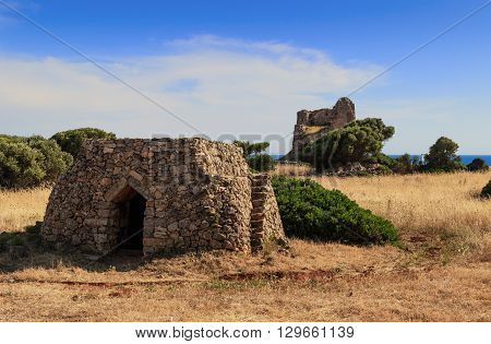 SALENTO LANDSCAPE.Trullo house:in the background Uluzzo watchtower .Apulia,Italy.These singular houses, used as temporary or daily shelters,are disseminaded all over the Salentine area.