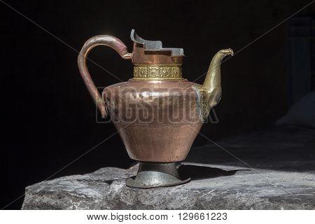 Old handmade tibetan pitcher on black background close up. India Ladakh