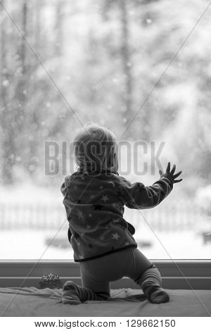 Black and white image of a toddler kneeling by the glass door inside the house looking out at snowflakes falling from the sky.